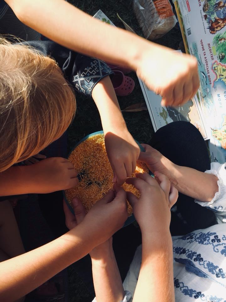 Діти торкаються до кукурудзяної крупи